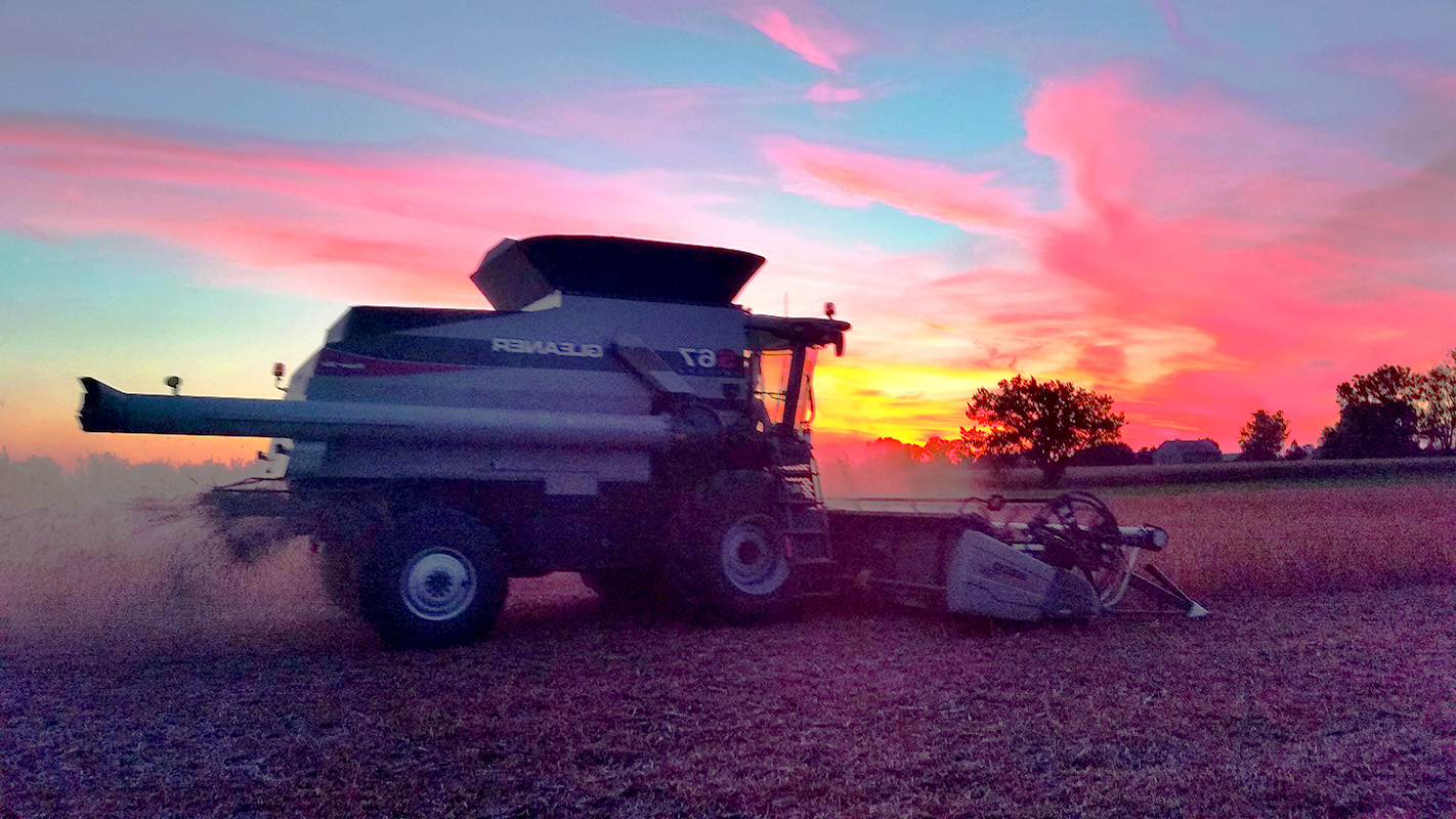 Combine in fields at sunset