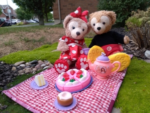 Two teddy bears sitting down on a picnic blanket