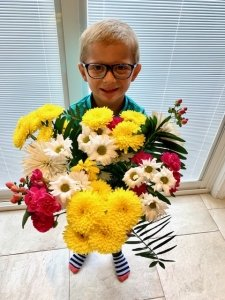 A young boy holding a vase of flowers