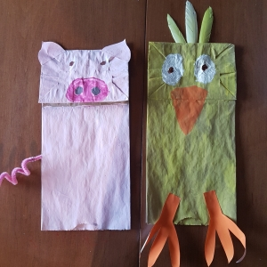 Two paper bags decorated as a chick and a pig puppet