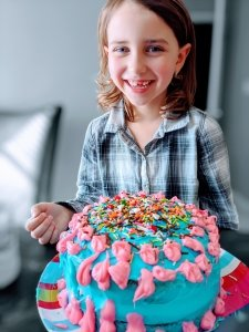 A blue and pink cake covered in sprinkles with a smiling girl