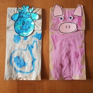 Two paper bags made into cow and pig puppets