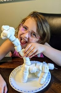 A giraffe made out of marshmallows with a smiling girl.