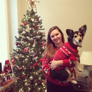 A girl in a red sweater holding a dog wearing a red sweater in front of a decorated christmas tree