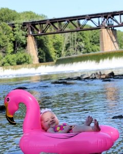 A baby laying on the river in a unicorn floaty