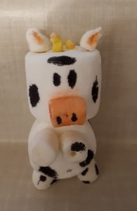 A small cow made out of marshmellows