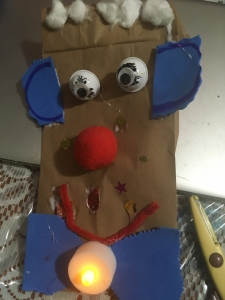 A paper bag decorated as a puppet
