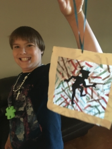 A young smiling boy holding up a peter pan suncatcher