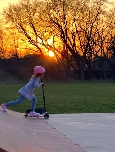 Scooter at sunset on a skate park
